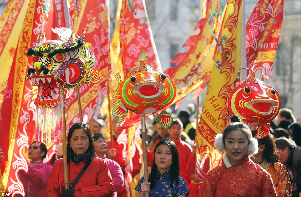Beautifully adorned flags were carried through London during the  celebration. Some members of the procession held delicately crafted dragon and carp heads suspended on poles. In Chinese mythology, carp are believed to be able to transform into dragons. One woman (centre) can be seen wearing a blue figure-hugging traditional Chinese dress known as a cheongsam, while another festival-goer (right) keeps the cold away with a pair of fluffy white ear muffs