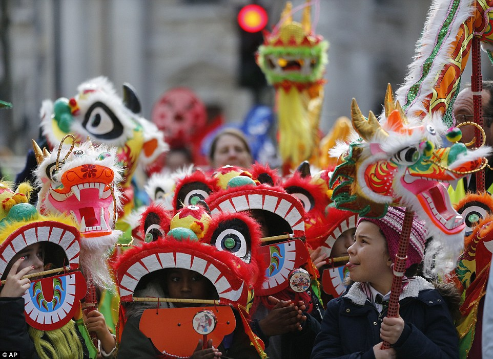 Londoners could be seen wearing dragon masks over their heads with holes where the mouth is so they could see where they were going. One boy (right) carried a colourful miniature version of the dragon with stark golden horns